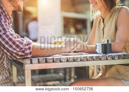 Young couple holding each other hands in coffee shop - Two lovers sitting and toasting beers in cafe restaurant - Love and travel concept - Focus on man's hand - Raw vintage filter