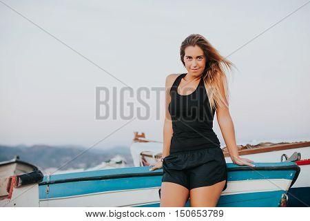 Blonde woman posing in sportswear at the seashore.