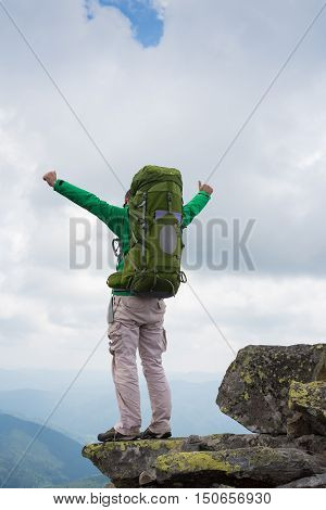 Happy tourist standing with backpack on a mountain top with raised up hands. Concept of success . Happy hiker winning reaching life goal success freedom and happiness achievement in mountains.