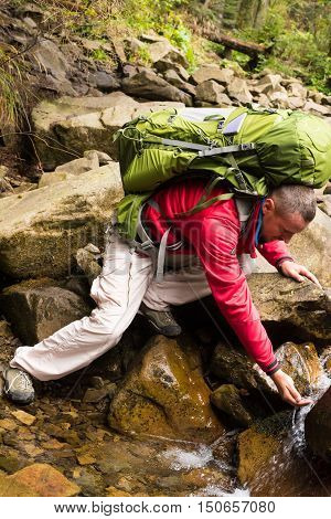 Hiker bending to take a drink from the mountains stream in the countryside. Man drink water from river in the wild. The concept of healthy lifestyle. Man taking water from mountain spring on hiking trip