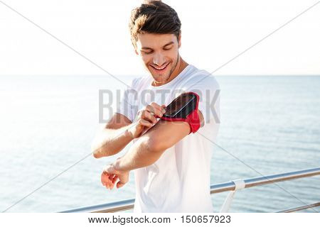 Smiling young sportsman using blank screen mobile phone on armband outdoors