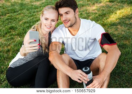 Portrait of sport man and woman making selfie in park while sitting on green grass and resting after jogging