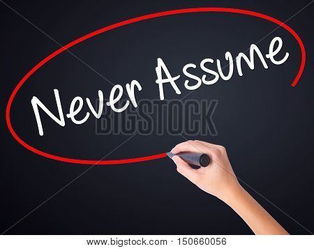 Woman Hand Writing Never Assume With A Marker Over Transparent Board .