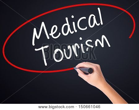 Woman Hand Writing Medical Tourism With A Marker Over Transparent Board