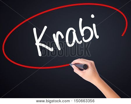 Woman Hand Writing Krabi  With A Marker Over Transparent Board .