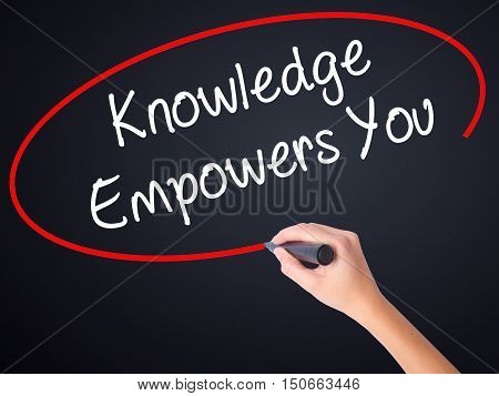Woman Hand Writing Knowledge Empowers You With A Marker Over Transparent Board