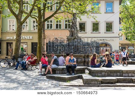 Bamberg Germany - May 22 2016: Tourists and local near the fountain with a statue of Neptune on Greenmarket Square. Bamberg is under UNESCO protection.