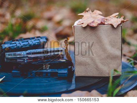 Autumn composition paper box mock up vinyl records tape cassettes fallen leaves