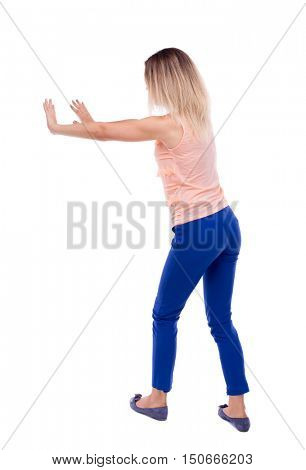 back view of woman pushes wall.  Isolated over white background. Rear view people collection. backside view of person. The blonde in a pink t-shirt shoves his hands in the side.
