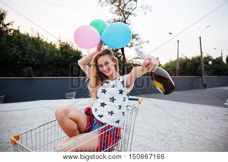 Happy smiling girl sitting in shopping cart with balloons and bottle of champagne