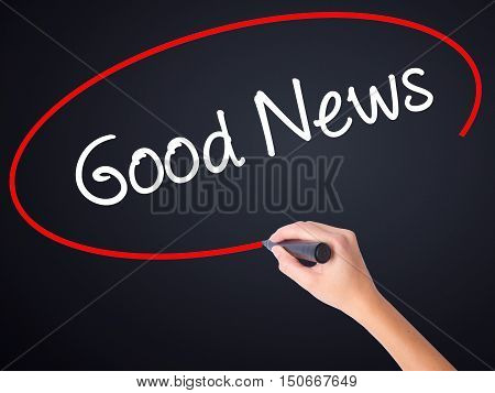 Woman Hand Writing Good News With A Marker Over Transparent Board