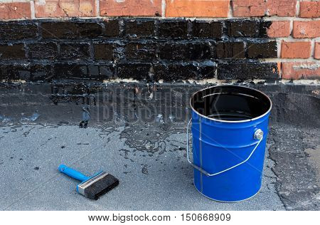 Tools for waterproofing. ceiling brushes and a bucket of bitumen primer