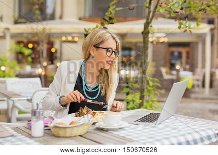 Business woman eating lunch and working on laptop