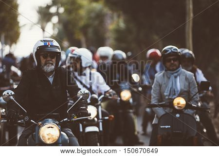 ALICANTE SPAIN - SEPTEMBER 25 2016: Middle aged rider on motorcycle is ready to start the race near a big group of riders on the Distinguished Gentleman's Ride day a global fundraiser for prostate cancer and men's health investigation