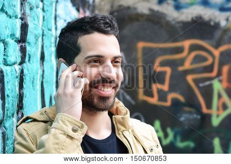 Portrait of young latin man talking on the phone against colorful wall. Outdoors.