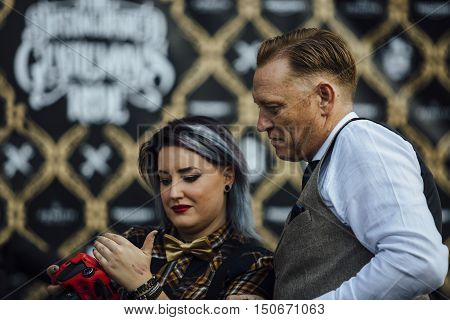 ALICANTE SPAIN - SEPTEMBER 25 2016: Stylish woman photographer is showing his work on her camera to a man on the Distinguished Gentleman's Ride day a global fundraiser for prostate cancer and men's health investigation.