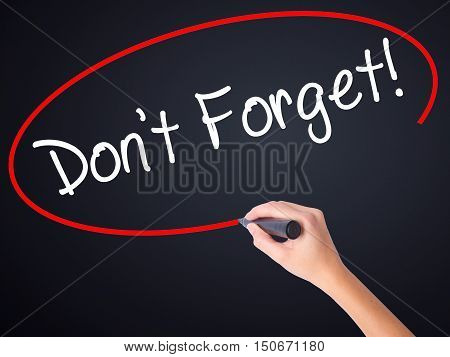 Woman Hand Writing Don't Forget!  With A Marker Over Transparent Board