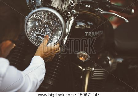 ALICANTE SPAIN - SEPTEMBER 25 2016: Detail of the hand of a man is putting a movember moustache sticker on the headlight of his motorcycle on the Distinguished Gentleman's Ride day a global fundraiser for prostate cancer and men's health investigation.
