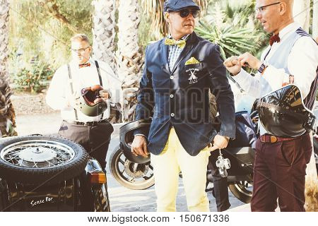 ALICANTE SPAIN - SEPTEMBER 25 2016: Men dressed in dapper styles are talking while they are holding their helmets on the Distinguished Gentleman's Ride day a global fundraiser for prostate cancer and men's health investigation