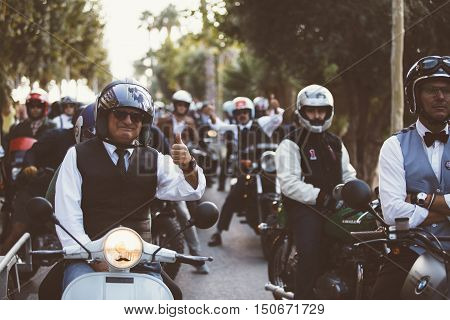 ALICANTE SPAIN - SEPTEMBER 25 2016: Middle aged rider on motorcycle is ready to start the race near a big group of riders and showing his thumb up on the Distinguished Gentleman's Ride day a global fundraiser for prostate cancer and men's health investiga