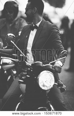 ALICANTE SPAIN - SEPTEMBER 25 2016: Smiling bearded young man is riding motorcycle on the Distinguished Gentleman's Ride day a global fundraiser for prostate cancer and men's health investigation. Black and white