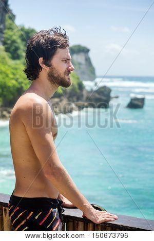 Portrait of male surfer looking into the distance of ocean from the top places on the coast
