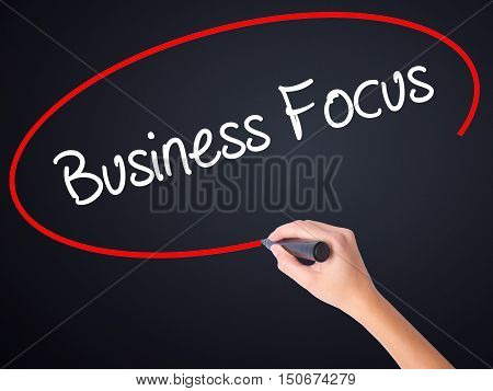 Woman Hand Writing Business Focus With A Marker Over Transparent Board .