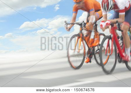 Group of cyclist during a race motion blur sky in the background