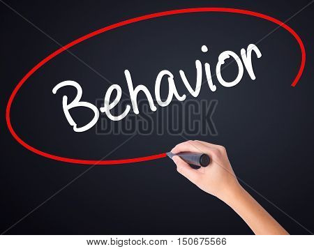 Woman Hand Writing Behavior With A Marker Over Transparent Board .