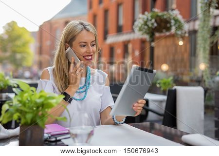 Business woman talking on the phone and using tablet