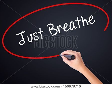 Woman Hand Writing Just Breathe With A Marker Over Transparent Board