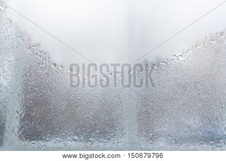 Window. The lower part of the window is covered with water droplets and is visible the window frame. The upper part of the window glass weeping and opaque.