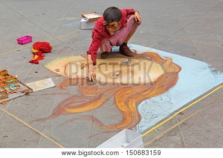 FLORENCE, ITALY - SEPTEMBER 2016 : Female artist painting Birth of Venus on pavement near Calimala street in Florence, Italy on September 21, 2016. Originally painted by Sandro Botticelli in mid 1480s