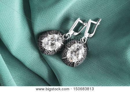 Diamond earrings on cyan silk as a background