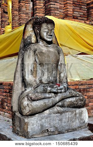 Lamphun Thailand - December 28 2012: A stone Buddha figure seated in Lotus position at the base of the Suwanna Chedi at Wat Phra That Haripunchai Maha Viham