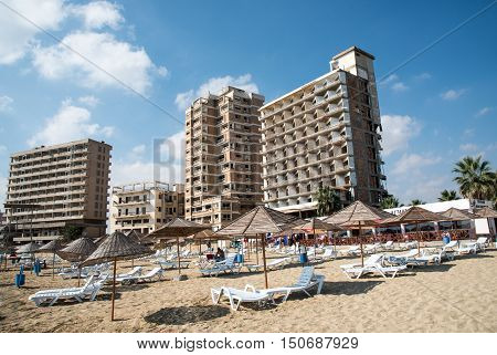 Famagusta Cyprus - September 15 2016: Palm Beach with beach umbrellas and tourists and the abandoned hotels at Varosha ghost town Famagusta Northern Cyprus