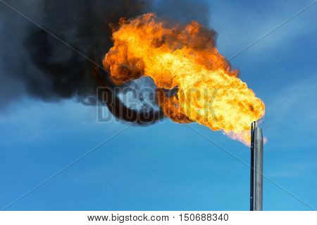 Torch against the sky. Combustion of associated gas at oil production.