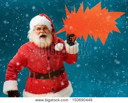 Monstrous Santa Claus showing red sign speech bubble banner looking unhappy and angry. Santa Claus on blue background. Merry Christmas & New Year's Eve concept.