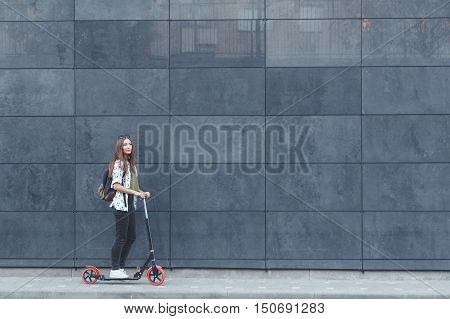 Joyful woman riding a kick scooter on modern fasade wall in background