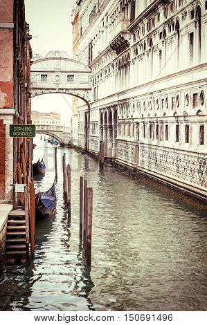 Photo of the Bridge of Sighs (Ponte dei Sospiri ) with gondolas dock in Venice (Italy). Photo is edited as a vintage with dark edges.