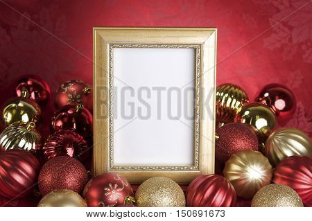 Christmas Background with an empty gold picture frame on a red background surrounded by red and gold balls