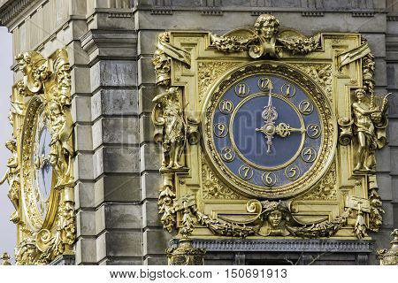 An ornate and ostentatious gold clock at 3pm