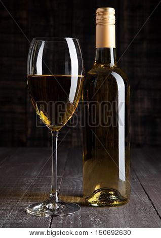 Bottle and glass of white wine on wooden board background