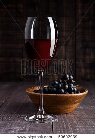 Glass of red wine with grapes in bowl on wooden board background