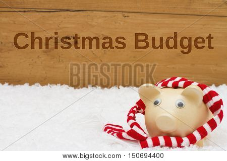 Having a Christmas Budget Piggy bank with scarf on snow with a weathered wood background with text Christmas Budget