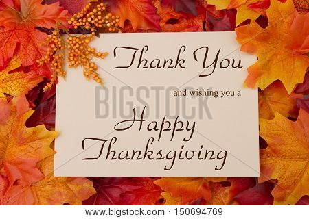 Happy Thanksgiving Message Autumn Leaves with a beige greeting card with text Thank You and Happy Thanksgiving