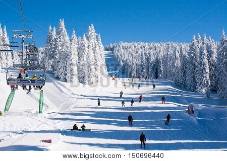 Kopaonik, Serbia - January 19, 2016: Ski resort Kopaonik, Serbia, ski slope, people on the ski lift, skiers on the piste among white snow pine trees