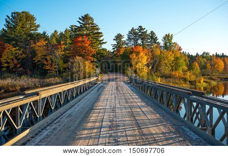 Early October, late afternoon sunshine on a portable deployable, single lane, steel and timber bridge over Cory Lake in Chalk River Ontario, Canada.