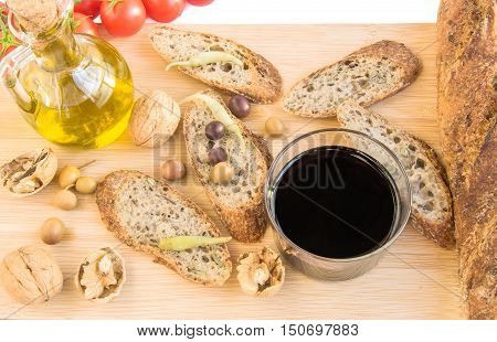 Home baked Alpine baguette nuts olives pepper glass of red vine and bottle of olive oil tomatoes