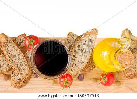 Home baked Alpine baguette olives pepper glass of red vine bottle of olive oil tomatoes